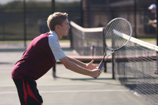 Senior Dylan Smith prepares to return during a serve.