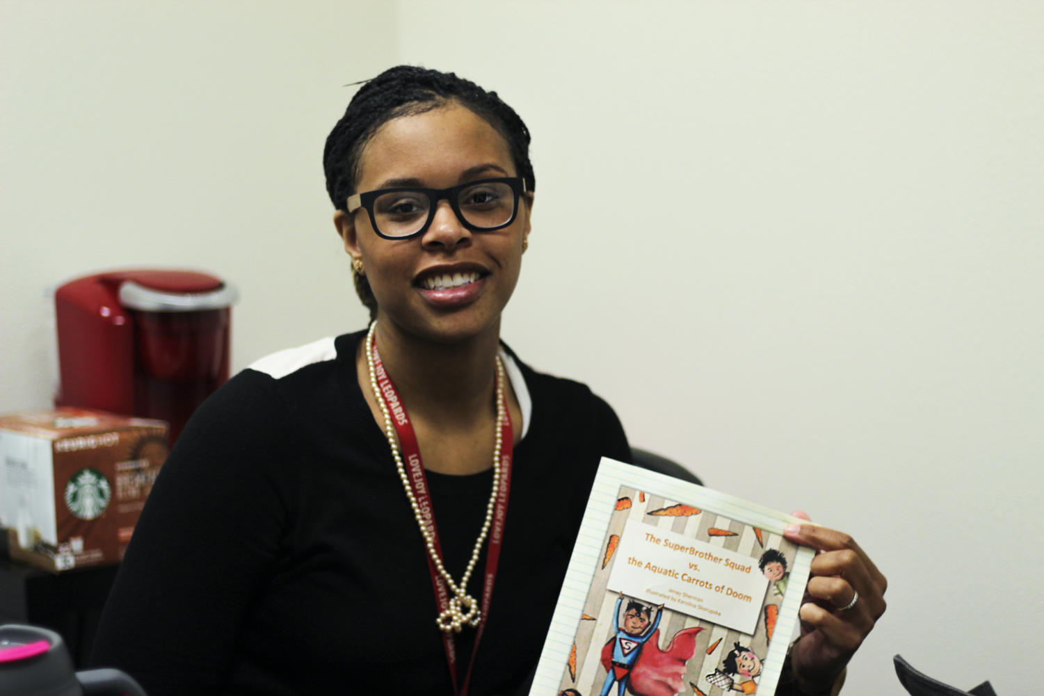 Leadership teacher Jenay Sherman poses with her self-published children's book.