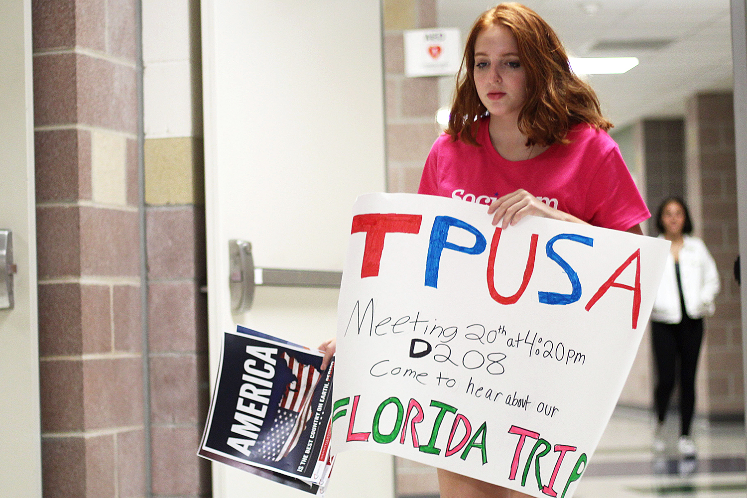 Sophomore Ariel Feldman hangs posters for the new Turning Point USA club before school on Wednesday, Sept. 12.
