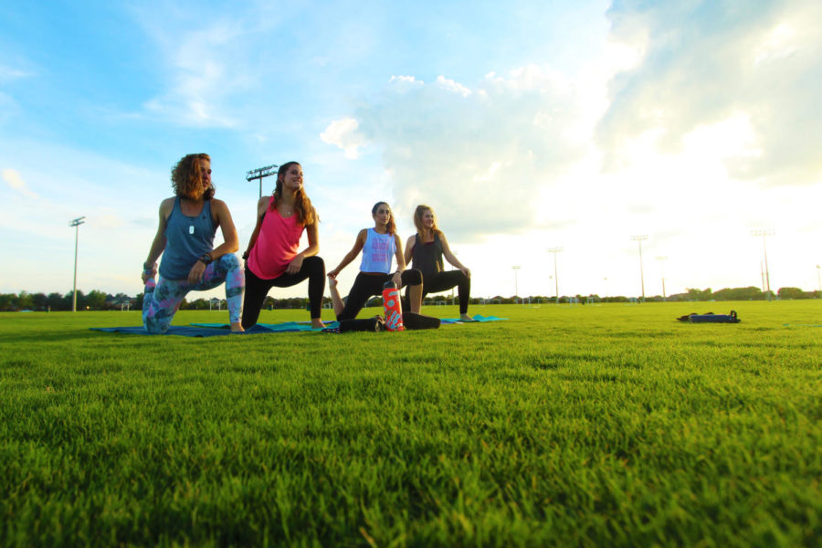 Yoga+club+members+Olivia+Bullock%2C+Hannah+Karst+%2C+Andria+Alyatim%2C+and+Caroline+Hanson+stretch+their+hamstrings+in+Celebration+Park.+