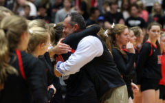 Head coach Jason Nicholson hugs senior Madison Waters as the team lines up on the court after the game.