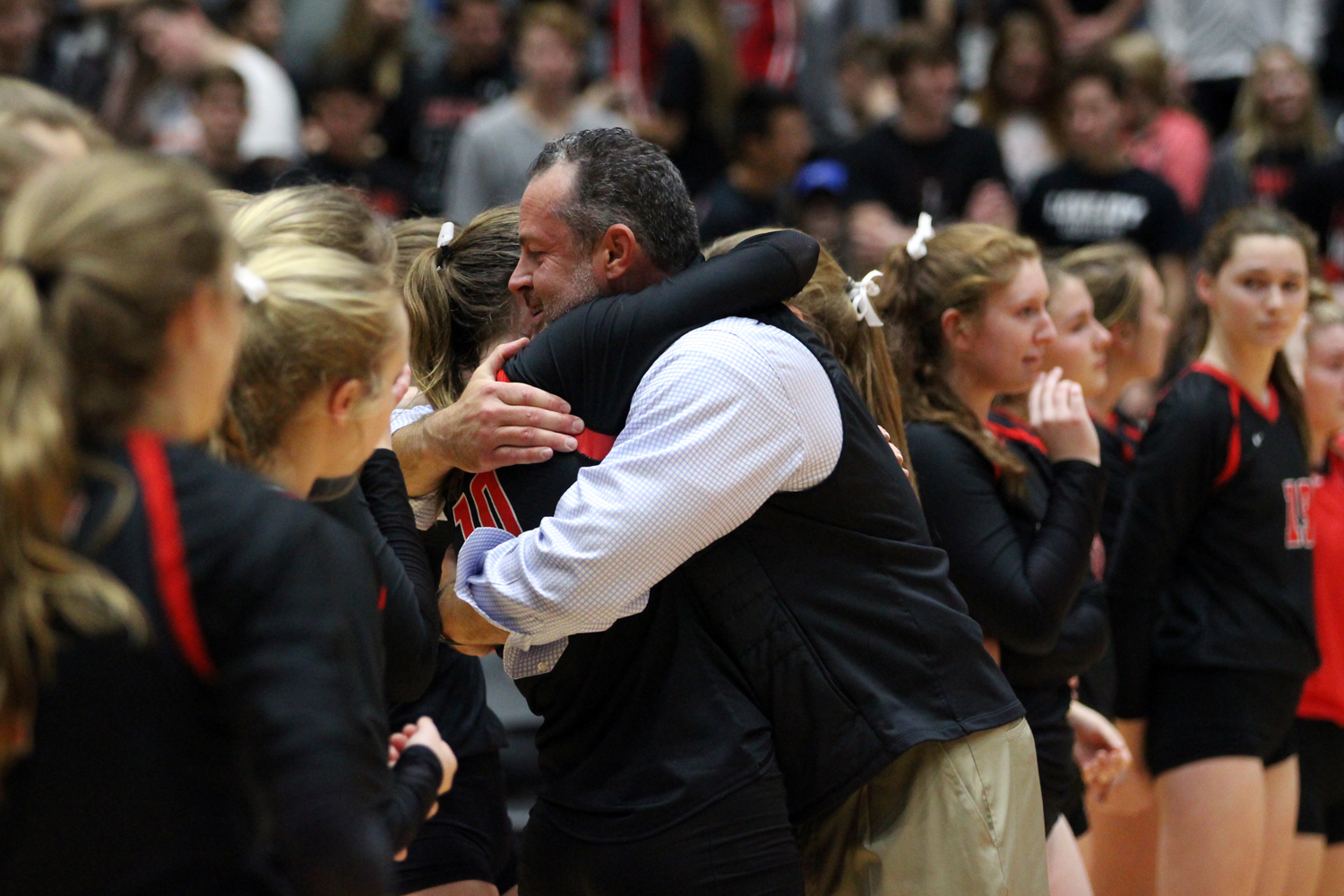 Head+coach+Jason+Nicholson+hugs+senior+Madison+Waters+as+the+team+lines+up+on+the+court+after+the+game.