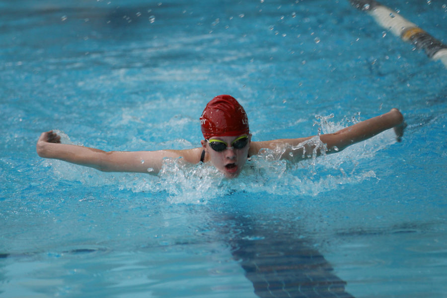 Junior Kelsey Carroll swims the butterfly at a meet.