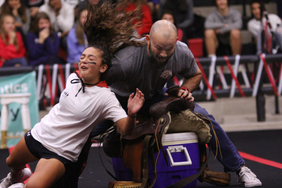Junior Reagan Matacle gets pushed out of her chair by reigning musical chairs champ coach Cole Kiefer.