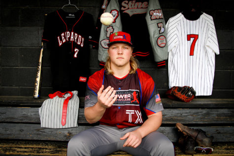 Catcher Luke Stine sits in the dugout with his past uniforms.