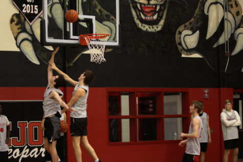 Senior Luke Ledebur contests a layup from sophomore Carson Holden in practice.