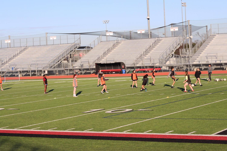 The girls soccer team runs drills.
