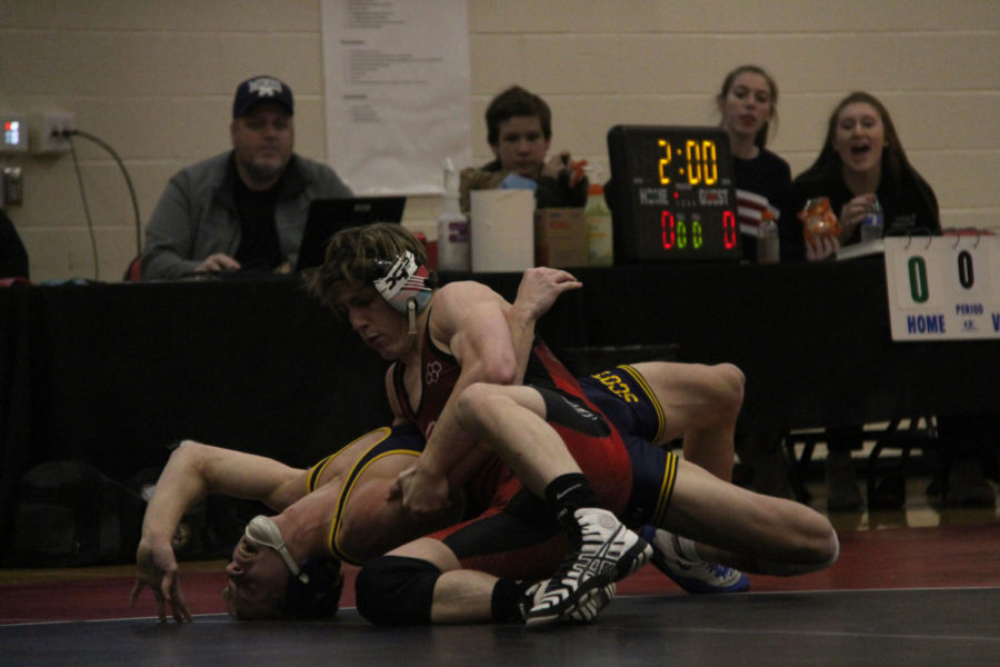 Hunter Duncan attempts to pin down a Highland Park wrestler.