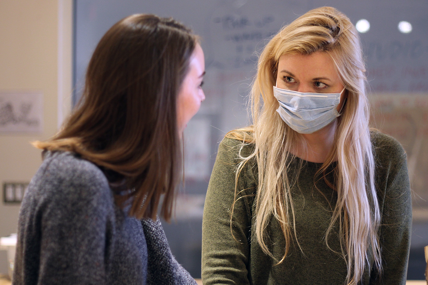 Art teacher Amanda Beller chats with senior Mallory Sailer in room E113 during eighth period on Thursday. Beller wore a mask during her classes this week as a precaution against the flu.
