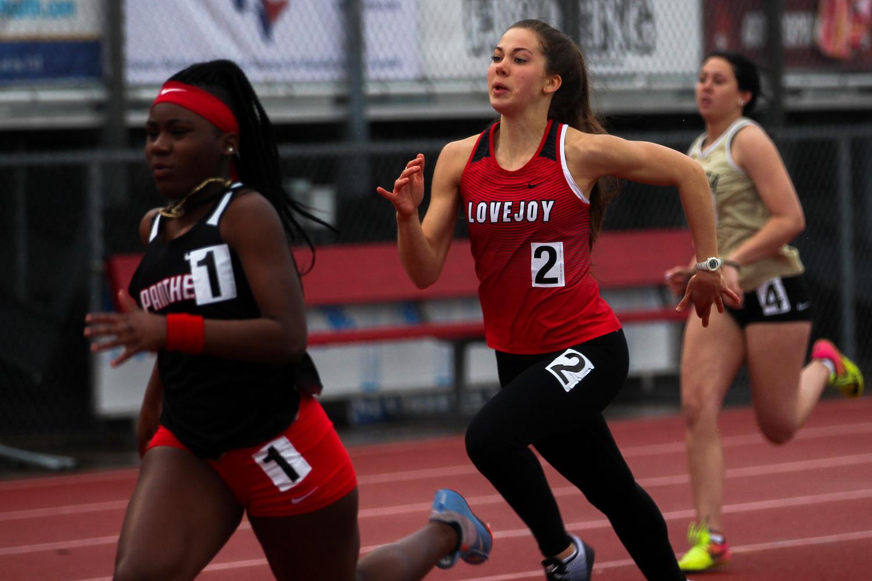 Junior Grace Bennett runs the 100 meter dash at the Lovejoy Invitational.