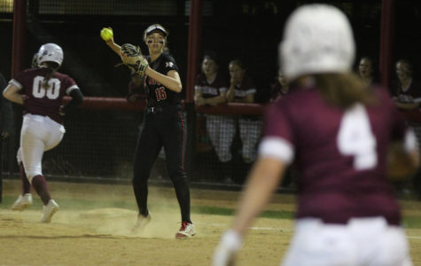 Senior Rebecca Holiman throws the ball back to the pitcher after getting it out at first.