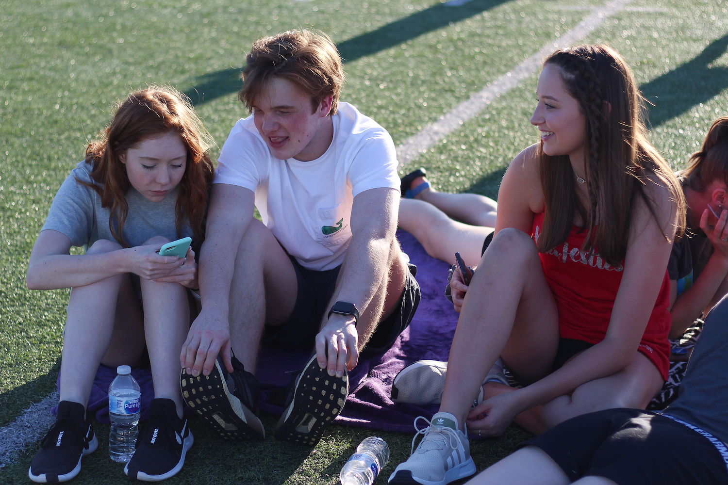 Juniors+Kaleigh+Knack%2C+Noah+Cooper+and+Lauren+Motsney+chat+while+sitting+together+on+the+field.