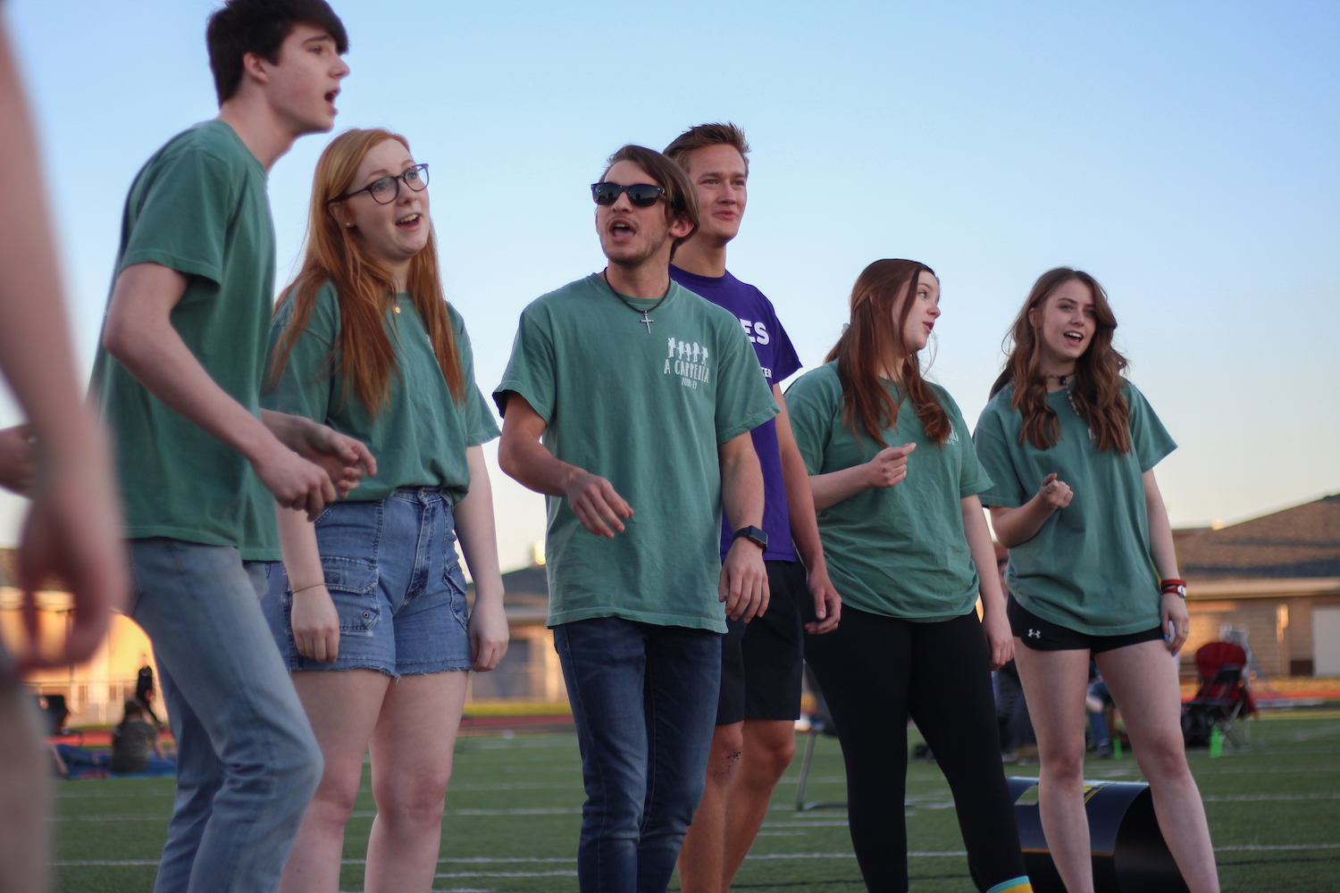A+Capella+member+and+junior+Christian+Cortez+looks+to+junior+Luke+Wild+as+they+perform+in+the+middle+of+the+field.+
