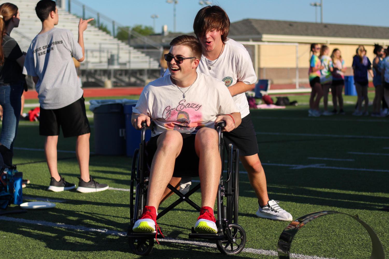 Law+Legg+pushes+Mason+Hartness+down+the+field+in+a+wheelchair.