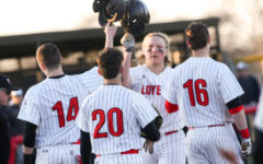 Senior Luke Stine celebrates with teammates at home plate after hitting an out of the park home run.