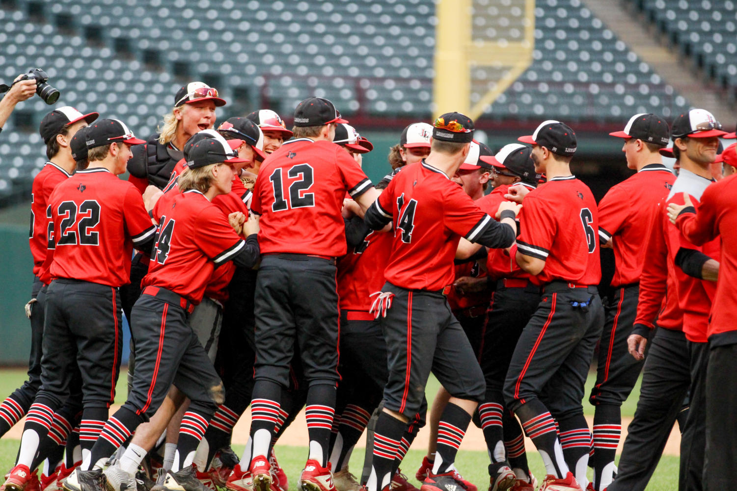 The+baseball+team+comes+together+in+the+middle+of+Globe+Life+Park+to+celebrate+their+playoff+win+against+Highland+Park.+The+Leopards+will+compete+against+Frisco+Lone+Star+in+their+round+three+series+of+games.