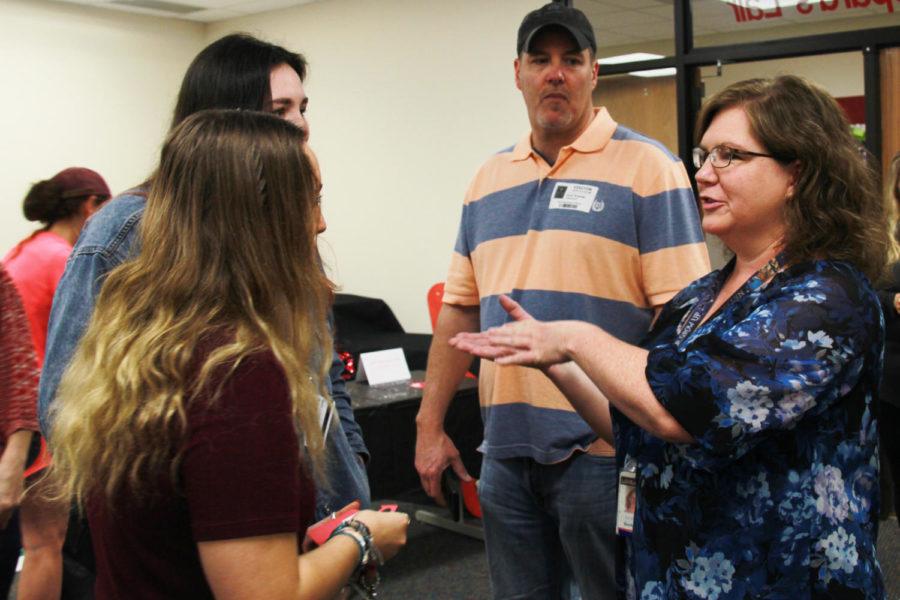 Seniors Faith Keane and Kyra Kramer greet current Hart art teacher Sharon Courtenay.