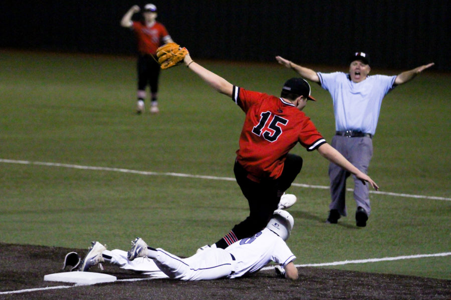 Junior Harrison Durow fails to make an out at first base as the umpire signals a safe gesture in the outfield.