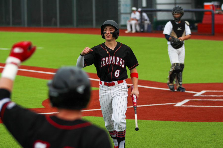Senior Luke Finn cheers after he scores a run in the third game of playoffs, bringing the score to 4-7.