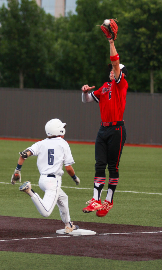 Senior Luke Finn jumps in order to make an out at first base against Lone Star player.
