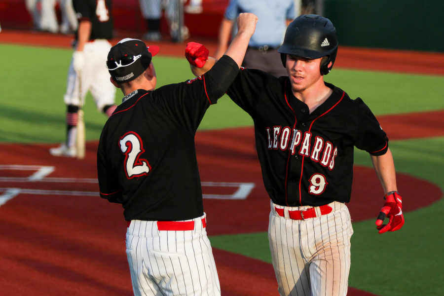 Junior Brett Sabin and Senior Jake Terwilliger lock arms as Terwilliger returns to the dugout as the Leopards transition to batting.