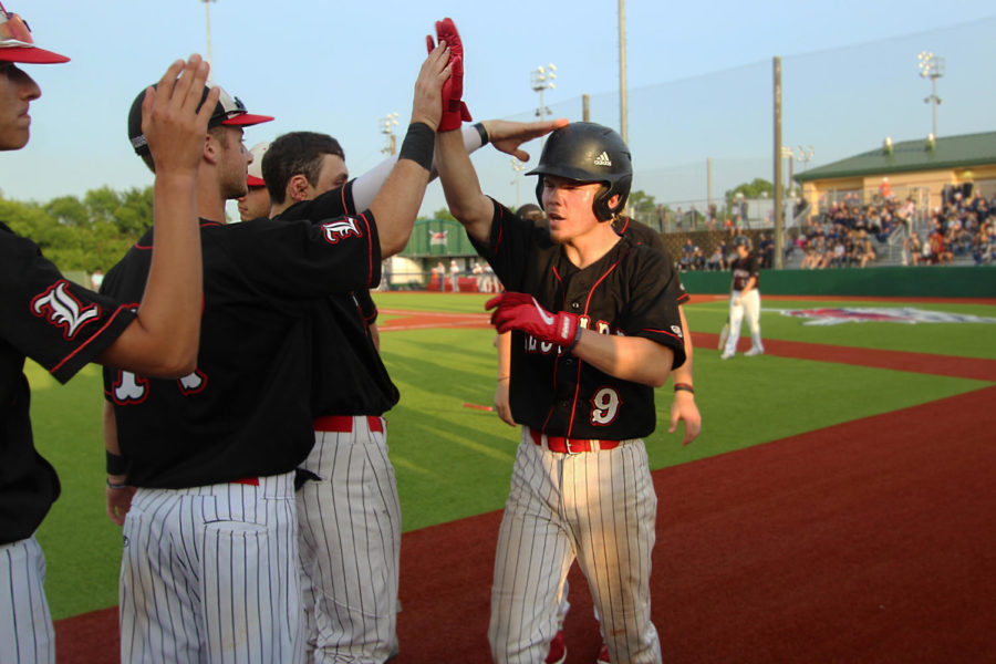 Senior Jake Terwilliger is greeted by junior Ben Nopper after a successful bat in the fourth inning.