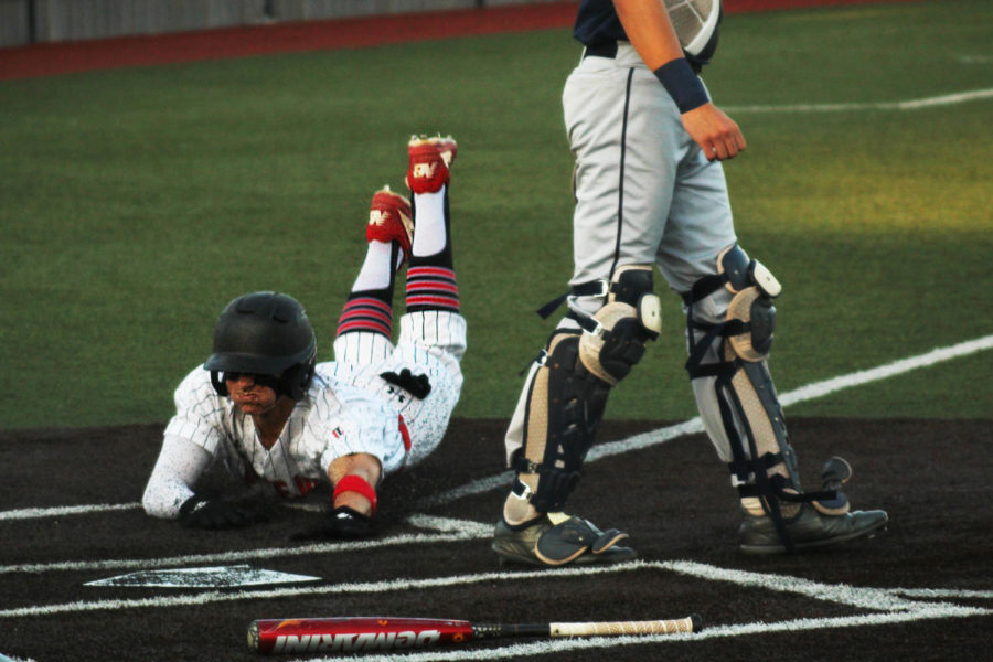 Senior Luke Finn slides into home plate following Luke Stine's successful bat in the sixth inning.