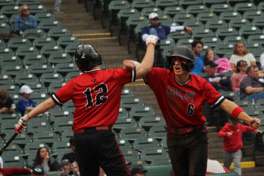Senior outfielder Zach Smith congratulates senior second baseman Luke Finn following his home-plate slide.
