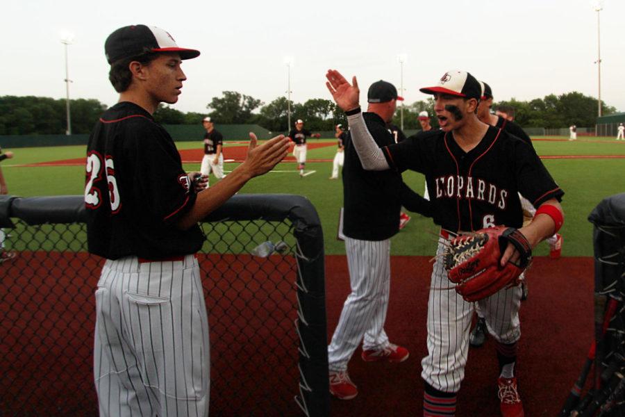 Junior Garrett Larson congratulates second baseman Luke Finn after the fifth inning as he enters the dugout.