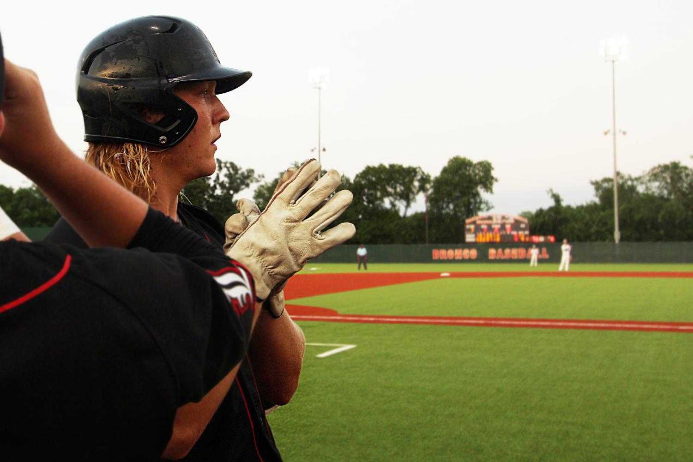 Senior+Luke+Stine+looks+on+as+he+prepares+to+take+the+field+to+bat.