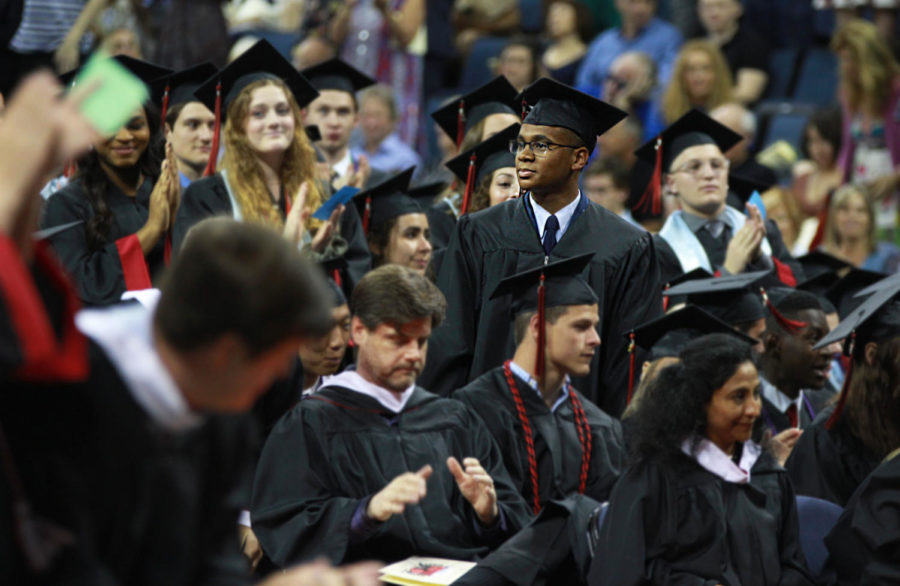 Graduate and future United States Air Force officer, Tyrese La Maison, watches his fellow graduates rise in a standing ovation to applaud him for his commitment to serve in the United States Air Force.