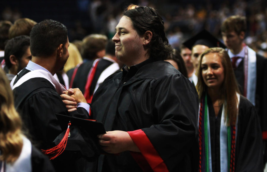 Graduate Logan Sigmon greets coach Vincent Hernandez as he exits the event center floor following the turning of the tassle.