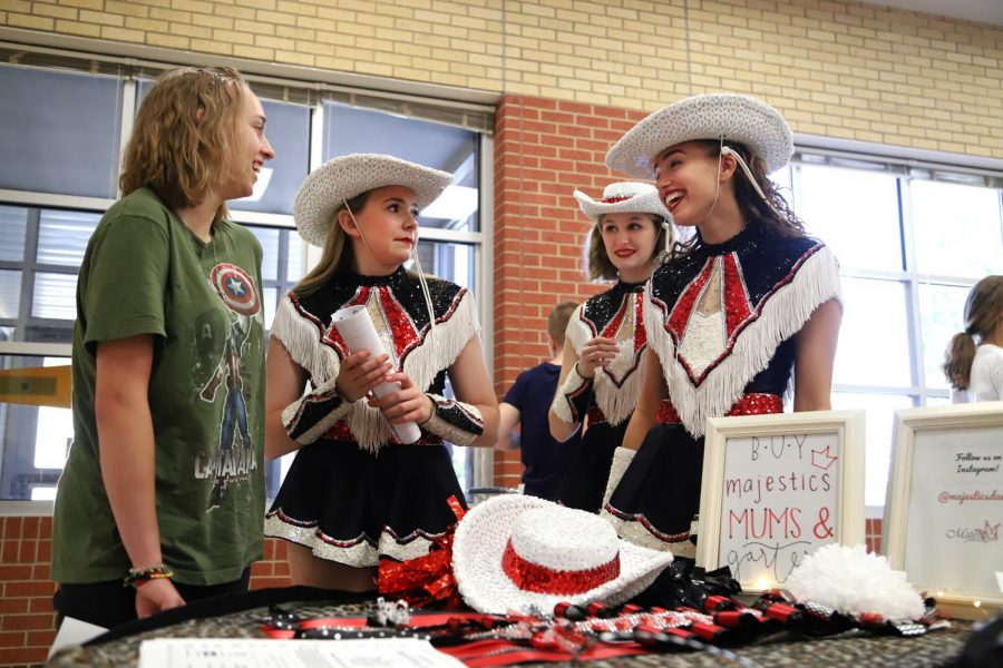 Junior Majestics Caitlin Debauge, Meredith Hughes, and Grace Baker greet an incoming freshman who is interested in trying out for the team. The Majestics are already preparing for their mum and garter sales, which will begin as homecoming nears.