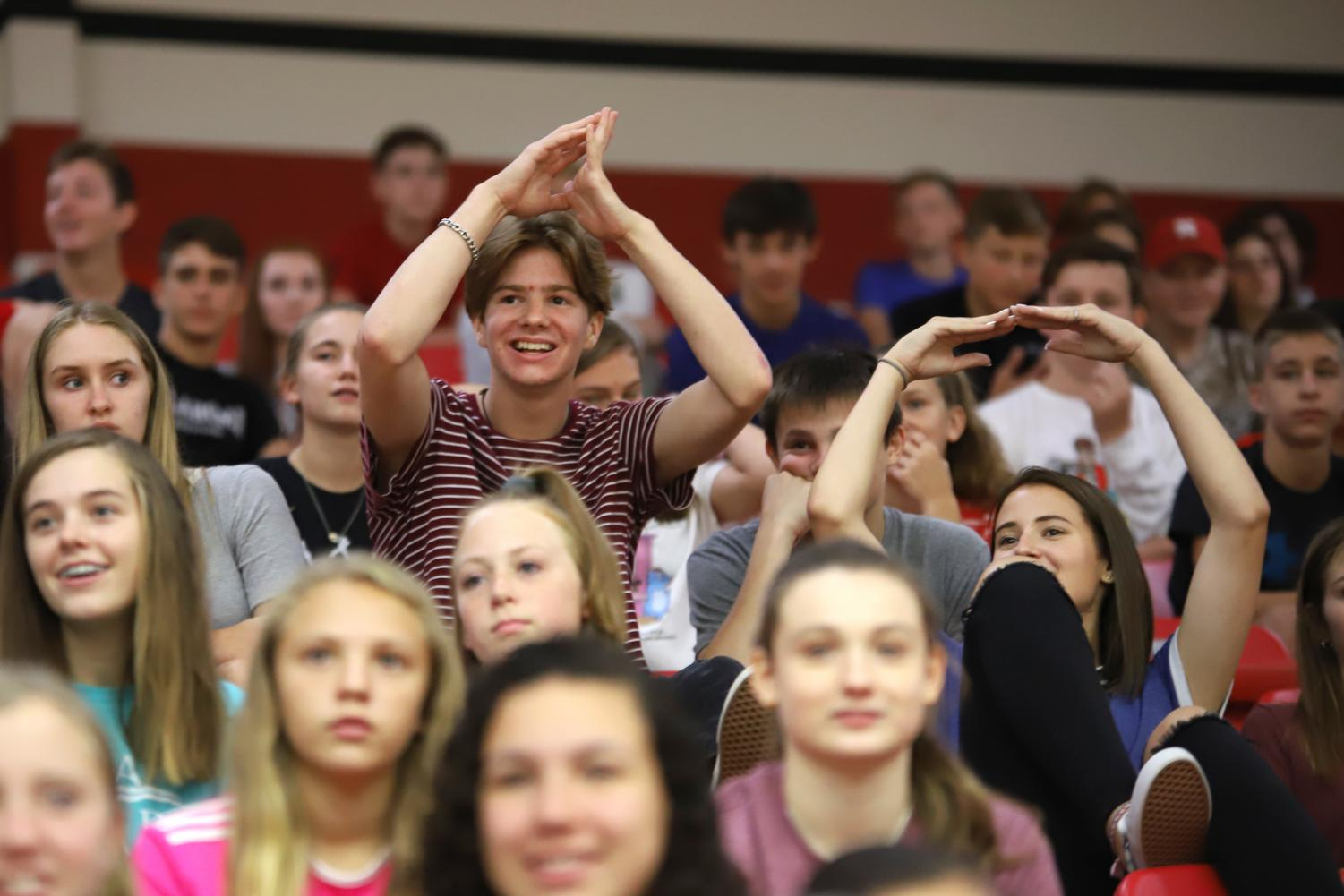 Freshman+Preston+Jones+and+Ashlyn+Martin+participate+in+the+A-O+chant+at+the+pep-rally.+Freshman+were+encouraged+to+stand+up+after+the+initial+explanation+of+the+chant.
