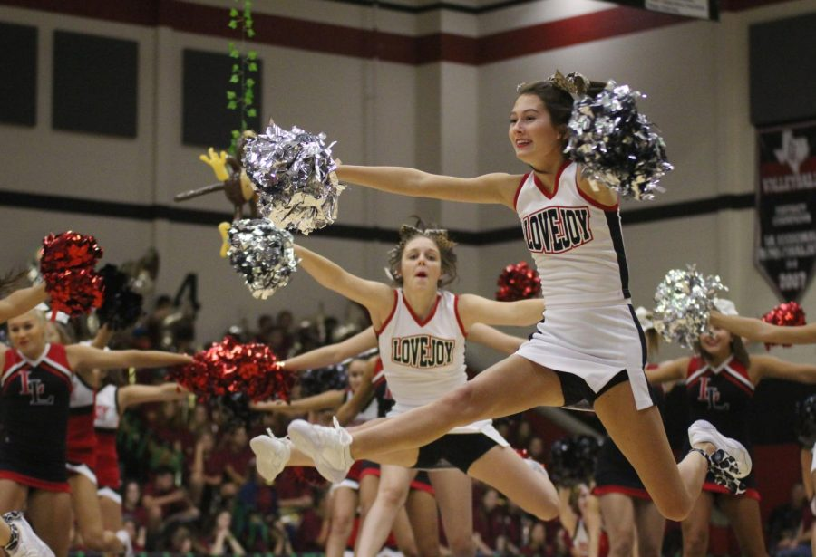 """Senior Addison Lloyd jumps into the air while performing. They cheer while a cover of """"Welcome to the Jungle"""" by Guns N' Roses was played through the speakers."""