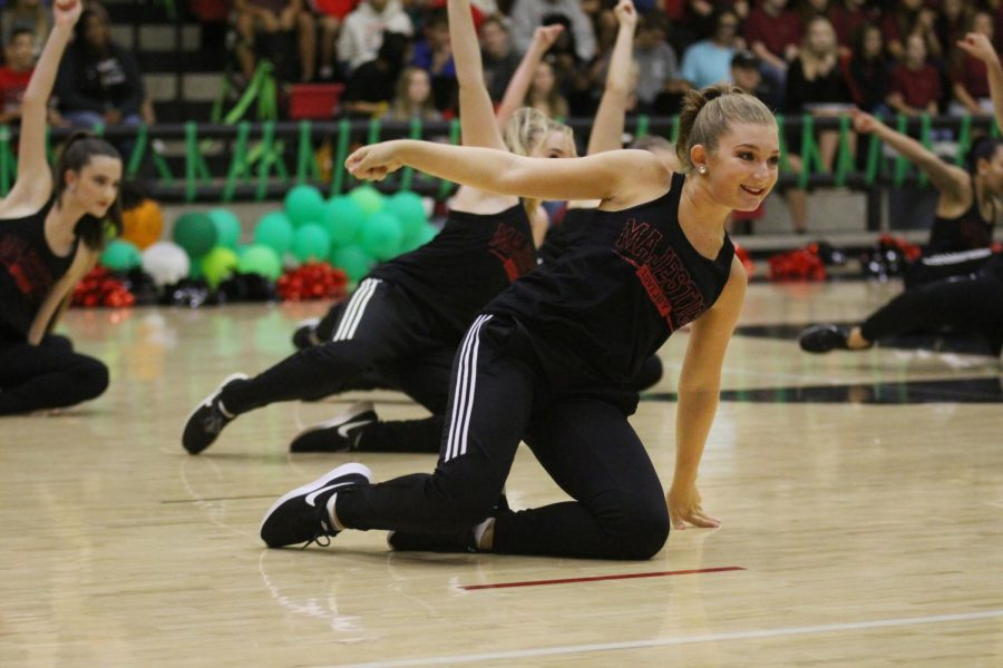 Junior Alexis Barajas slides across the floor dancing with the Majestics to a blend of several hip-hop songs. They will perform during half time on Saturday's football game.