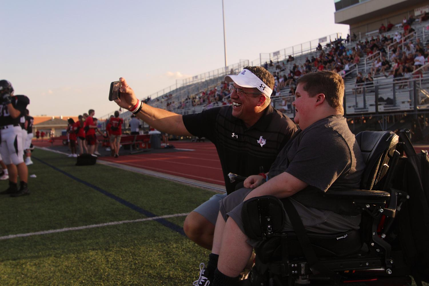Superintendent Dr. Mike Goddard takes a selfie with sophomore Reid White on the sideline before the first play. This is Goddard's first year as superintendent, and his iconic selfies express his enthusiasm for the position.