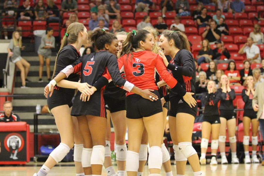 The volleyball team huddles after securing a point in a home matchup against Byron Nelson.