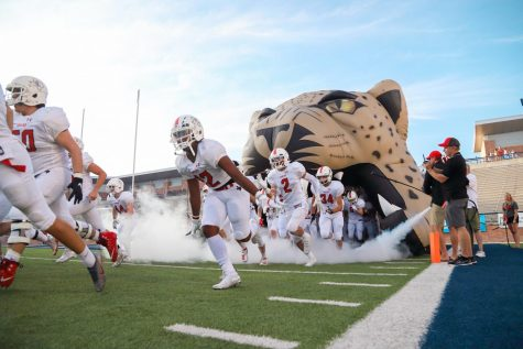 The Leopard football team runs out of the leopard head and onto the field. Because Lovejoy was the visiting school, the team ran out first before the Panthers and were led by Tyler Beidleman.