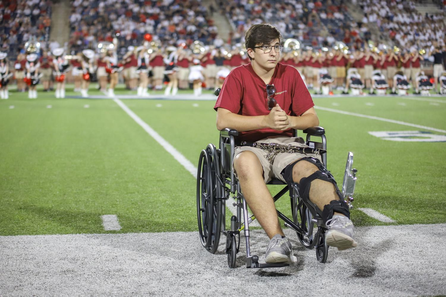 Freshman+Chris+Dechant+sits+on+the+sidelines+during+the+majestics+performance.+Dechant+was+unable+to+march+since+he+broke+his+knee+cap+in+the+band+hall+two+days+before+the+game.+Instead+of+marching%2C+Dechant+played+his+clarinet+in+the+front+next+to+the+front+ensemble+during+the+band+halftime+show.