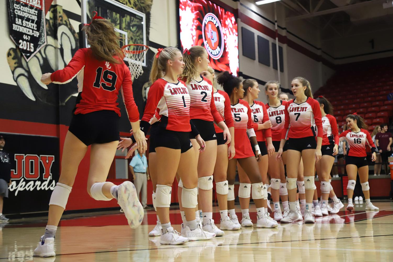Junior+Lexie+Collins+high+fives+senior+Mckenna+Franks+after+her+name+is+called+out+before+the+game.+Afterwards%2C+the+Leopards+stood+together+as+the+national+anthem+was+played.