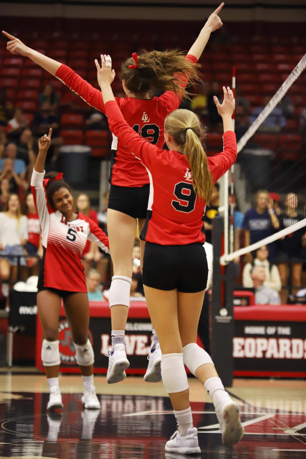 Junior+Lexie+Collins+and+sophomore+Averi+Carlson+celebrate+during+the+first+set+of+the+game.+The+Leopards+won+the+first+set+25-18.