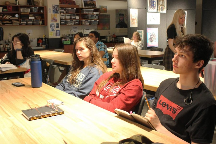 Junior Brynne Davies and seniors Marisa Medrano and William Floyd listen to Arianne Ohman present her slides at the Art History Club meeting Wednesday morning.