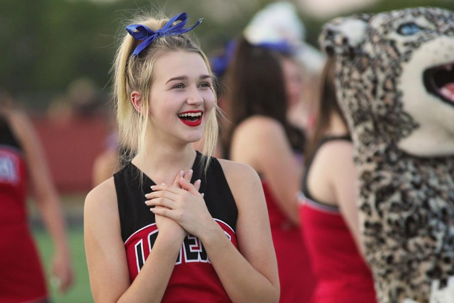 Varsity cheerleader Grace Felton laughs as Dirty Drumline member Matt Piccirillo dances with his flag. The Dirty Drumline stood with the school flags on the 40 yard line before the team took the field.