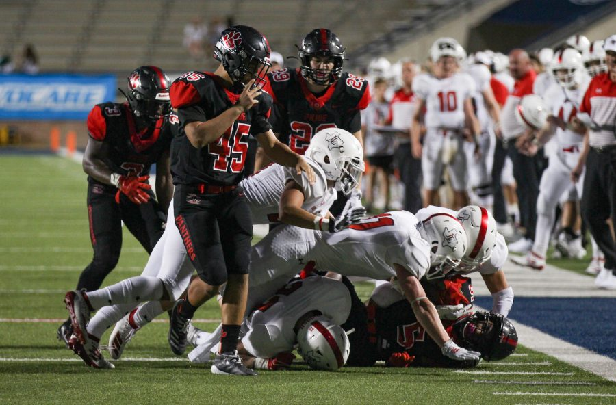 Colleyville Heritage offensive lineman Husam Elshiek is tackled by four Lovejoy football players at the sideline.
