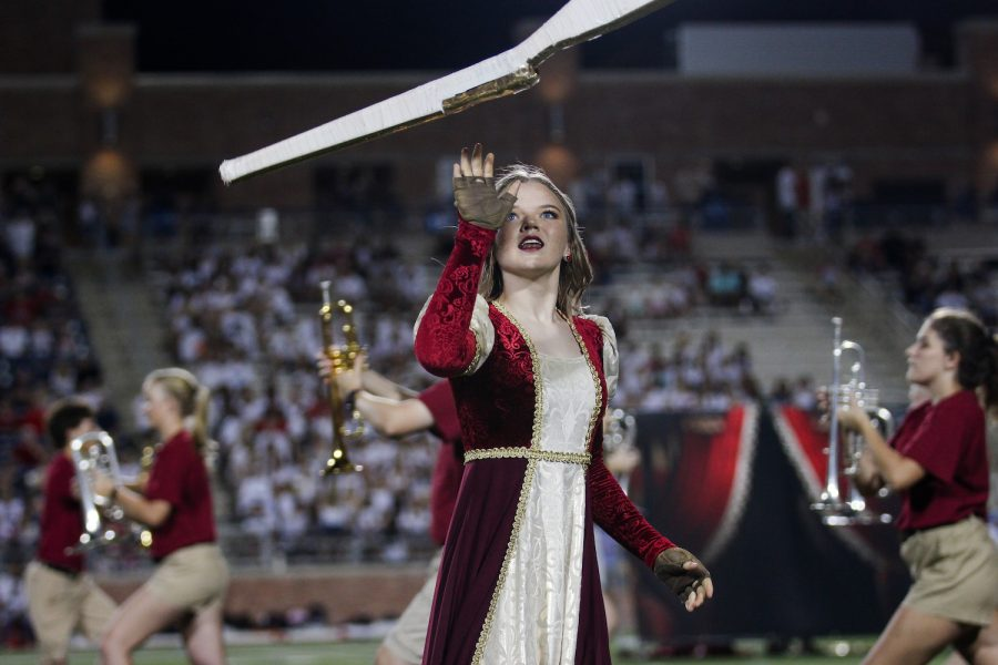 Sophomore Mackenzie Miller twirls her rifle as the band begins to encircle the color guard as part of their show, Juliet.