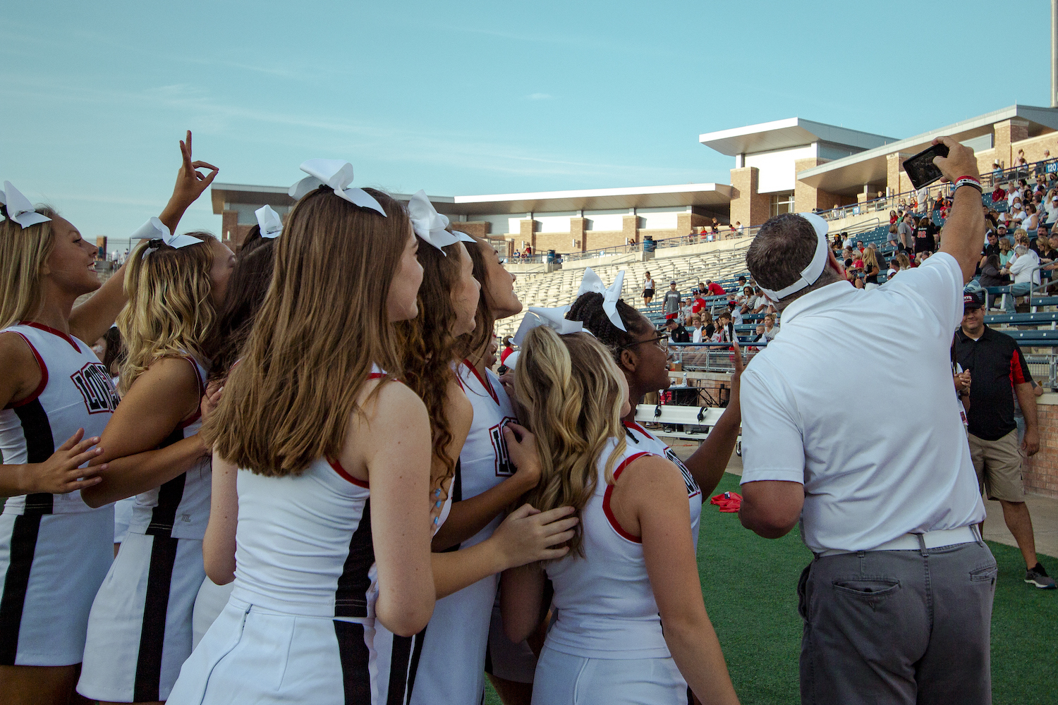 Superintendent+Dr.+Mike+Goddard+takes+a+selfie+with+the+cheerleading+team+while+the+football+team+warms+up+on+the+field.+