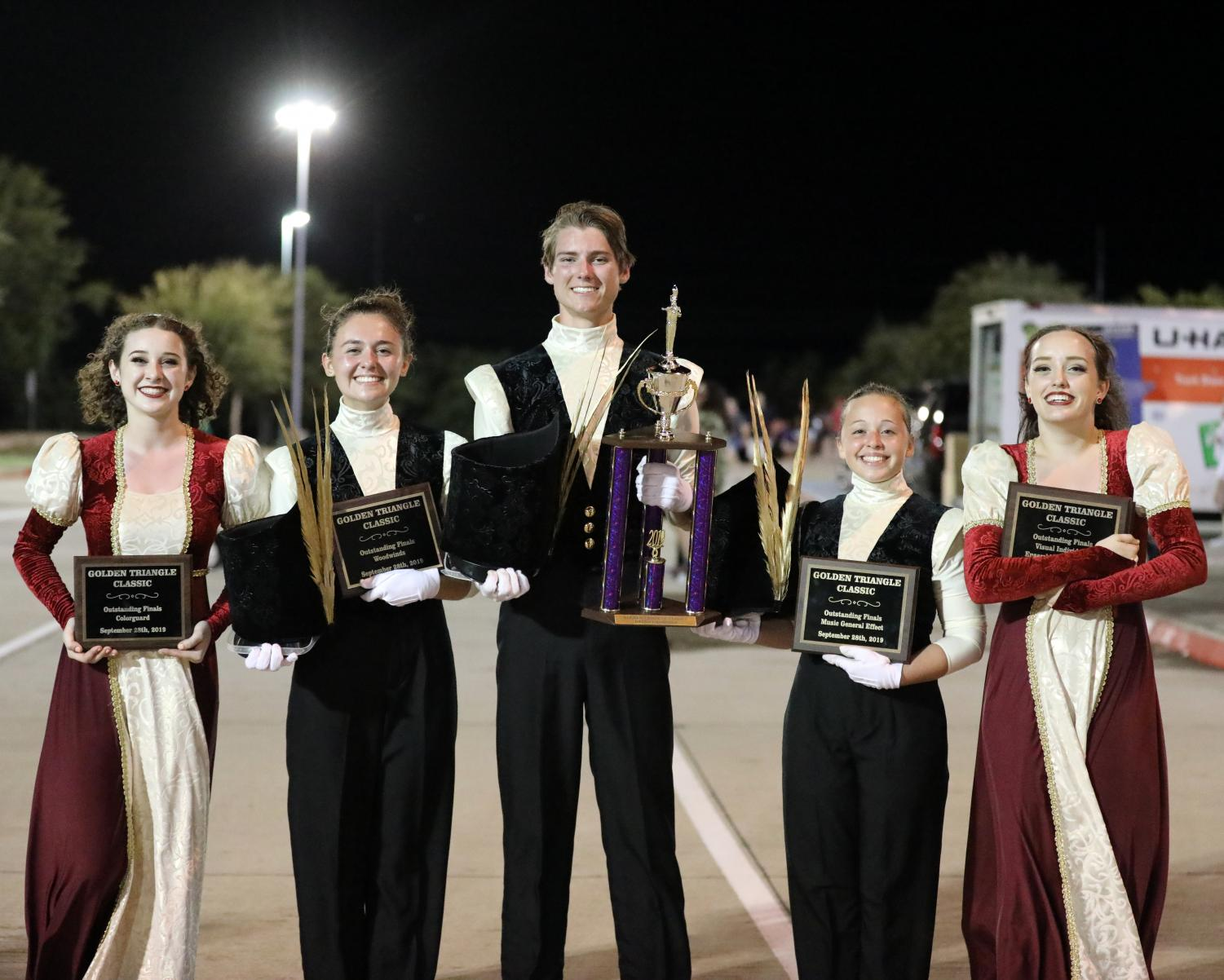 Guard Captain and junior Elise Bell, Drum Majors senior Lily Hager, senior Joe Harris, junior Catherine O'Brien, and Guard Lieutenant Jordan Sleeper smile outside the Golden Gate Triangle stadium after receiving the award for the first first place in the school's marching band history. The band also won the captions for colorguard, woodwinds, music general effect, and visual individual performance on that day, Sept. 28.