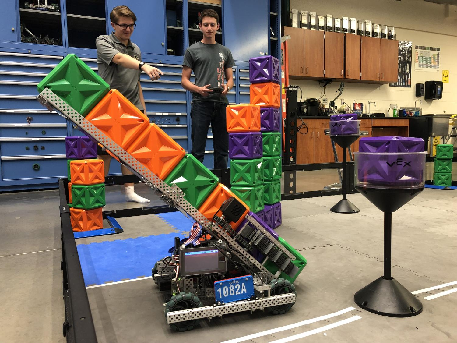 Senior Anthony Ciletti and senior Jake Bluestein practice for the competition by having the robot pick up cubes.