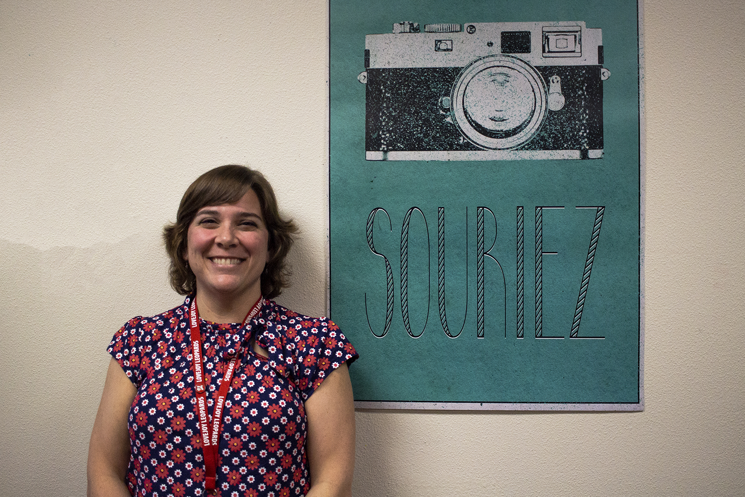 "French teacher Billie Kelsey stands in front of a poster in her room that says ""smile"" in French, as it's one of her favorite classroom decorations as a new teacher."